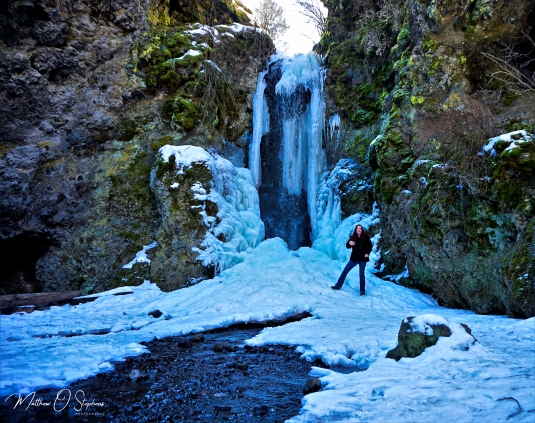 Sarah next to the half frozen falls